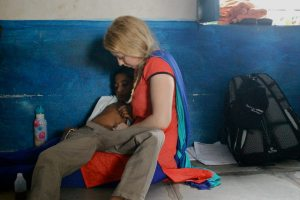 Treating a boy with constipation on the floor of a school due to lack of tables.